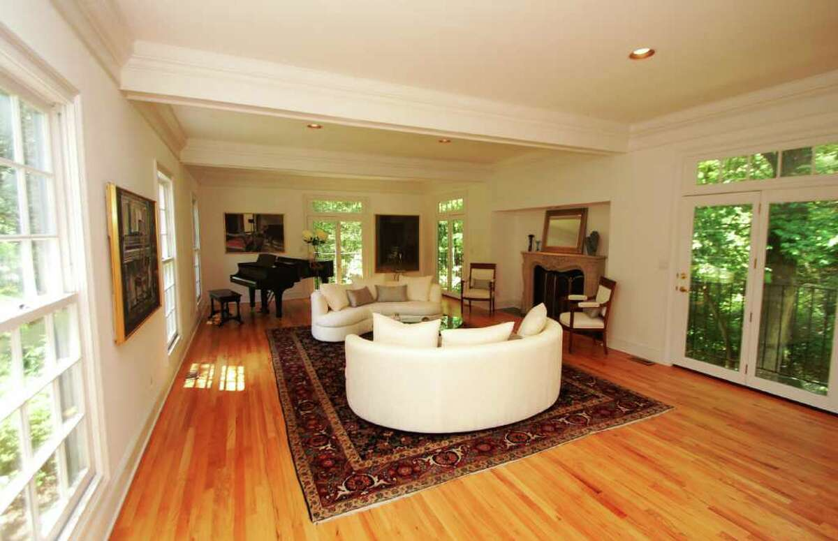 The formal living room, as seen through the foyer, features over-sized, nine-over-nine, double-hung windows, a marble fireplace, exposed beams, deep crown molding and three sets of double French doors.