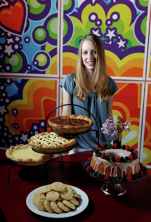 Leanna Fossler poses with an assortment of her pastries including a cream cheese pound cake, pecan pie a Texas Peach and Blueberry pie, and a Buttermilk pie at Heights Ashbury Coffeehouse, a bakery-coffeehouse where her pastries soon will be sold, Friday, Aug. 5, 2011,in Houston. Behind Fossler is artwork by Charlie Hardwick. ( Karen Warren / Houston Chronicle ) Photo: Karen Warren / © 2011 Houston Chronicle