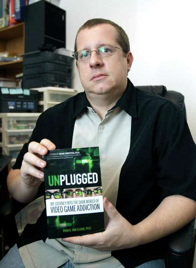 "In this June 3, 2011 photo, Ryan Van Cleave holds a copy of his book ""Unplugged"" at his home in Sarasota, Fla. Gaming and thinking about video games was all-consuming for Van Cleave. Yet living inside the game World of Warcraft, which became his obsession, seemed preferable to the drudgery of everyday life. Especially when the life involved fighting with his wife about how much time he spent on the computer. While the game made him feel ""godlike,"" life's small hitches could be ""profoundly disempowering."" Despite thoughts like this, recorded in a new book, despite dissociative episodes in supermarkets when he felt as if he was inside a game, he did not think he had a problem IRL _ gamerspeak for In Real Life. But he did, and a reckoning was coming. (AP Photo/Chris O'Meara) Photo: Chris O'Meara / AP"