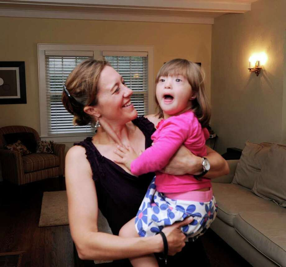 Julie Cevallos holds her daughter, Nina, 2, in their Greenwich home, Friday afternoon, Sept. 23, 2011. Nina's image, along with images of children and adults from around the world with Down syndrome, will be shown on the big screen at Times Square on Saturday prior to the National Down Syndrome Buddy Walk in Central Park. Photo: Bob Luckey / Greenwich Time