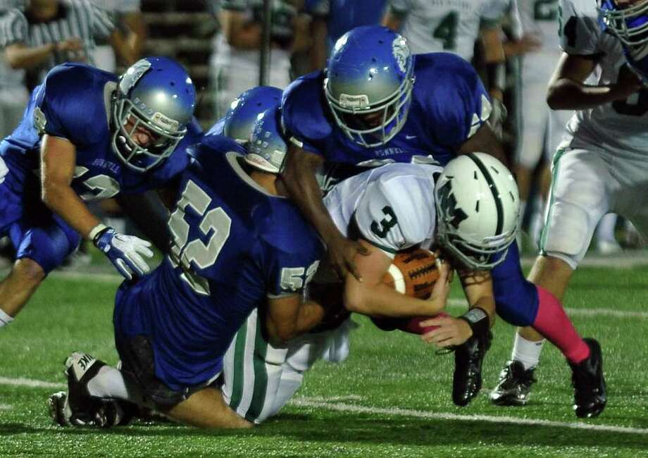 Several Bunnell players sack New Milford QB Conor Shanahan, during boys football action in Stratford, Conn. on Friday September 23, 2011. Bunell players are #13 Andrew Calzone,, left, #52 Do Nguyen, center, and #54 Rashaun Rosario. Photo: Christian Abraham / Connecticut Post