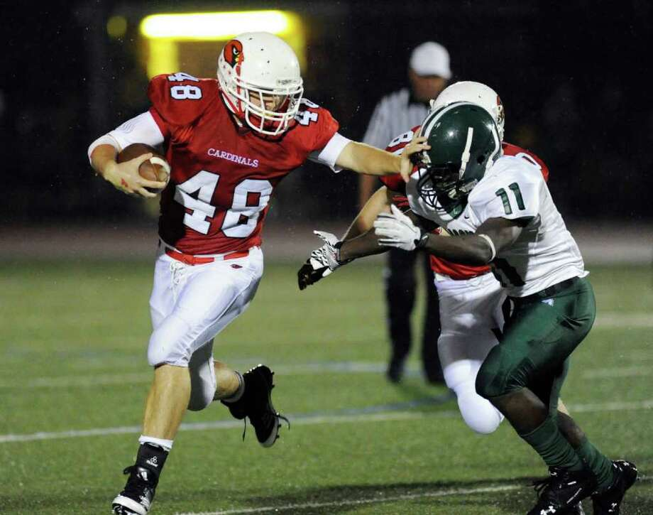 Shane Nastahowski, # 48 of Greenwich High School, stiff-arms Tevin McFadden, # 11 of Bassick High School, during football game between Bassick High School of Bridgeport and Greenwich High School at Greenwich, Friday night, Sept. 23, 2011. Photo: Bob Luckey / Greenwich Time