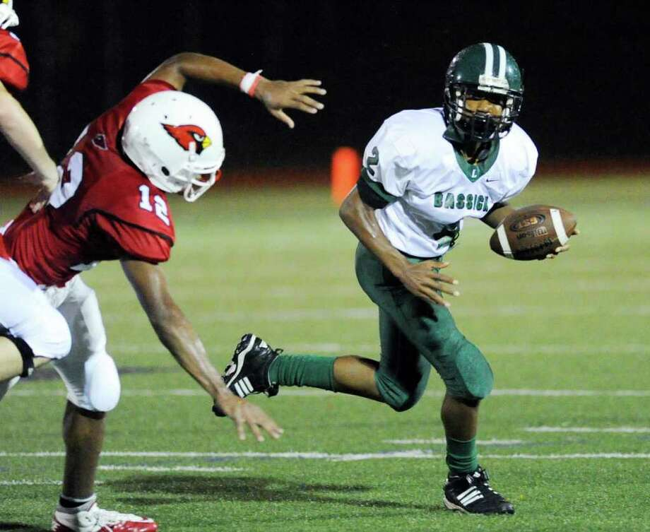 Bassick High School quarterback Vochan Fowler, right, # 2, breaks the corner past Greenwich defender Elijah Dume, # 12, during  football game between Bassick High School of Bridgeport and Greenwich High School at Greenwich, Friday night, Sept. 23, 2011. Photo: Bob Luckey / Greenwich Time