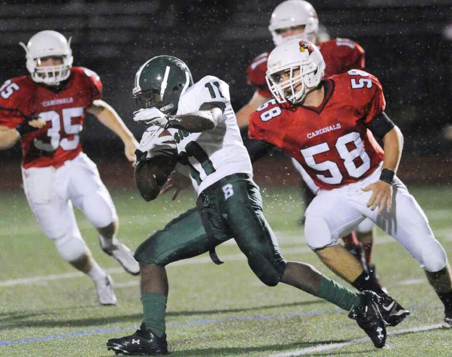 Tevin McFadden, # 11 of Bassick High School gets tackled by Alex McGee, # 58 of Greenwich High School during football game between Bassick High School of Bridgeport and Greenwich High School at Greenwich, Friday night, Sept. 23, 2011.  At left for Greenwich is Mark Bernstein # 35. Photo: Bob Luckey / Greenwich Time