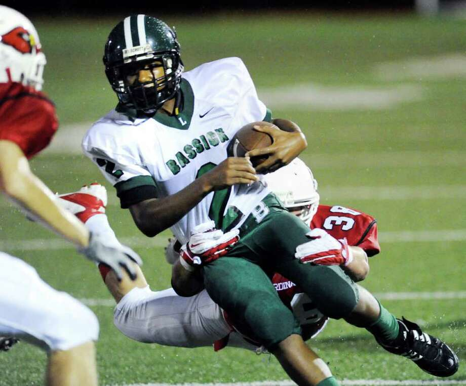 Bassick quarterback Vochan Fowler, # 2, is tackled by Dan Claroni, # 38 of Greenwich High School during football game between Bassick High School of Bridgeport and Greenwich High School at Greenwich, Friday night, Sept. 23, 2011. Photo: Bob Luckey / Greenwich Time