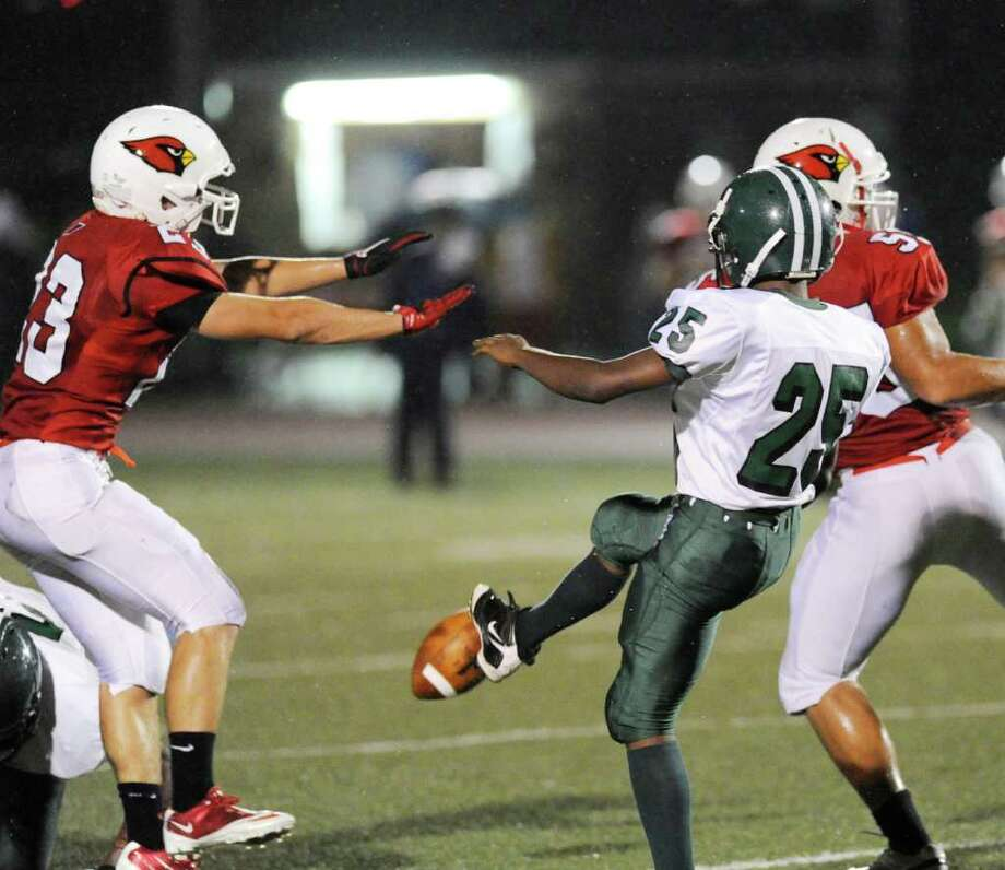 Bassick High School punter, Vonte Riddick, # 25, gets his kick blocked during football game between Bassick High School of Bridgeport and Greenwich High School at Greenwich, Friday night, Sept. 23, 2011.  At left is Mike Daly, # 23 of Greenwich, at right is teammate Kyle Camacho, # 55. Photo: Bob Luckey / Greenwich Time