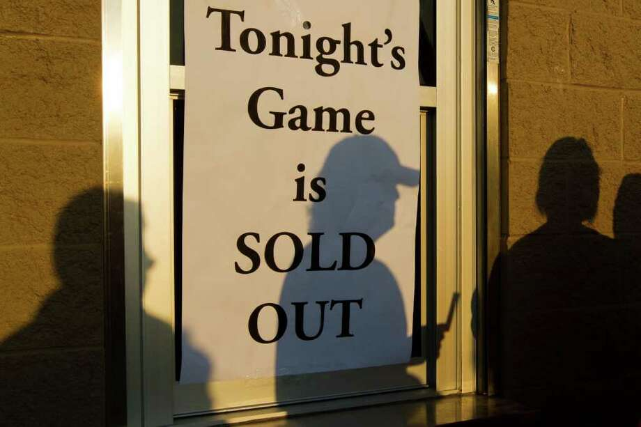 "Lucky fans holding tickets cast a shadow on a closed ticket window covered by a sign reading ""Tonight's Game is SOLD OUT"" as they wait to enter Bulldog Stadium for a high school football game between Deer Park and La Porte. Photo: Smiley N. Pool, Houston Chronicle / © 2011  Houston Chronicle"