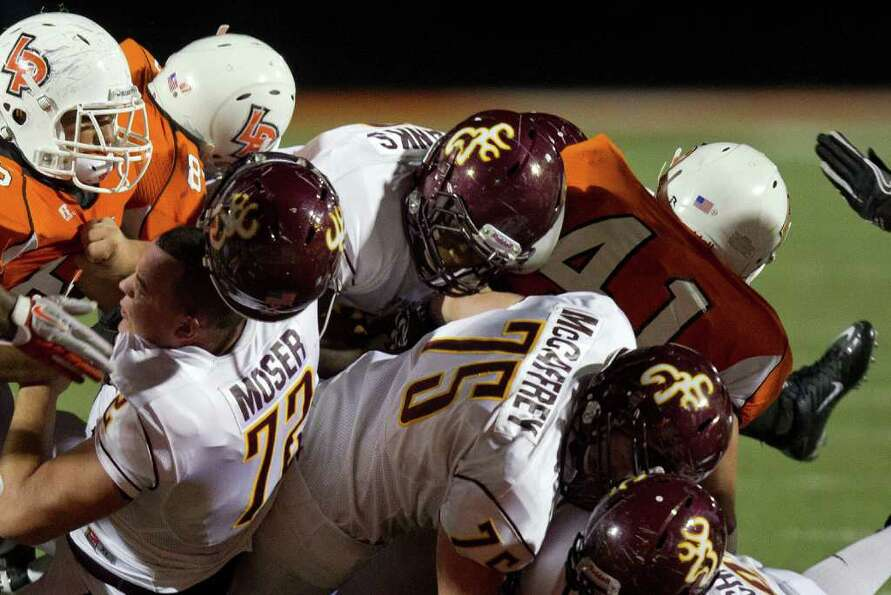 Deer Park offensive lineman Chance Mosure (77) loses his helmet as he blocks for running back Demetr