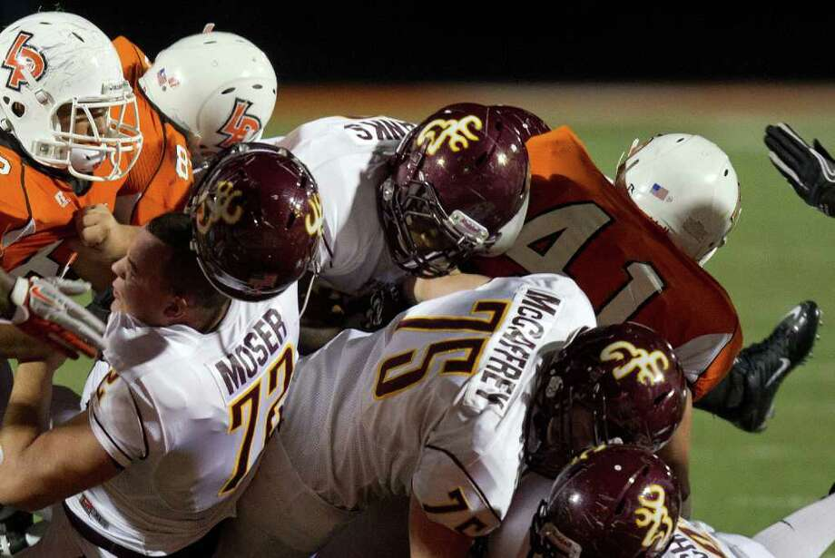 Deer Park offensive lineman Chance Mosure (77) loses his helmet as he blocks for running back Demetrius Banks goal line attempt during the first half. The Deers came up short but scored on the next play. Photo: Smiley N. Pool, Houston Chronicle / © 2011  Houston Chronicle