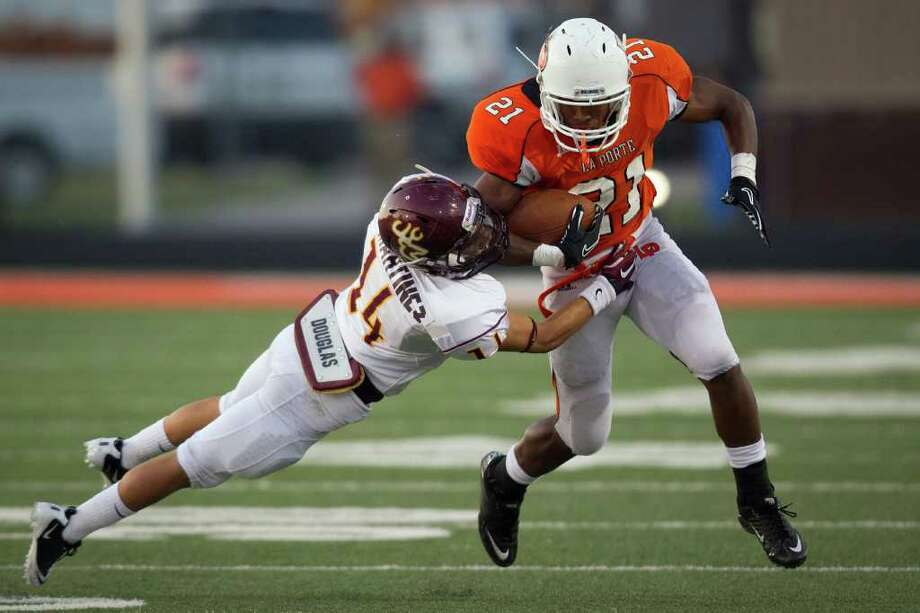 La Porte running back Keith Whitely (21) is hit by Deer Park defensive back Ryan Martinez (14) during the first quarter. Photo: Smiley N. Pool, Houston Chronicle / © 2011  Houston Chronicle