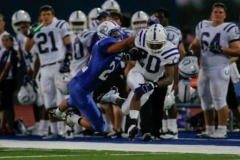 Dayton receiver Gamal Fowler (20) is tackeled by Barbers Hill safety Landon Sarria (22) Friday evening September 23, 2011 at Eagle Stadium in Mont Belvieu during the first night of District 19-4A play. Barbers Hill is undefeated  and Dayton is 2-1 going into the game. The Eagles lead 17-14 at the half.