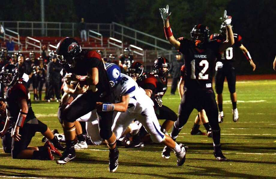 Fairfield Warde's Dario Pugliano (12) celebrates as teammate Joe Marx (44) pushes past Darien's defense Ian Vanderhorn (28) for a touchdown during the second quarter of the football game at Fairfield Warde High School on Friday, Sept. 23, 2011. Photo: Amy Mortensen / Connecticut Post Freelance