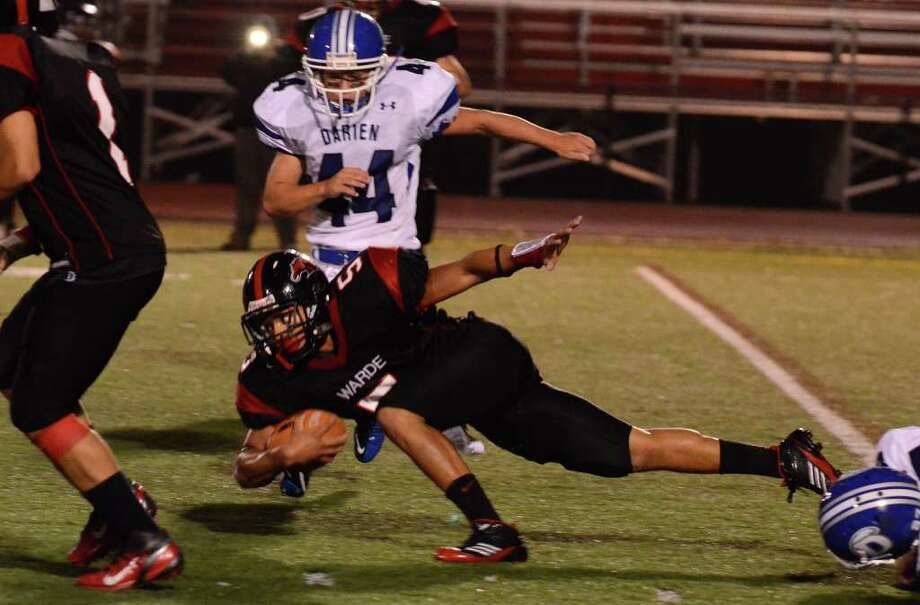 Fairfield Warde's Devin Lofton (5) gets low as he carries the ball for yardage during the football game against Darien at Fairfield Warde High School on Friday, Sept. 23, 2011. Photo: Amy Mortensen / Connecticut Post Freelance