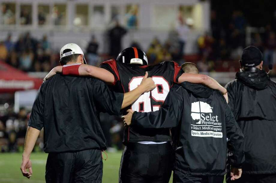 Fairfield Warde's Kevin Krug (89) is walked off the field after being tackled during the football game against Darien at Fairfield Warde High School on Friday, Sept. 23, 2011. Photo: Amy Mortensen / Connecticut Post Freelance