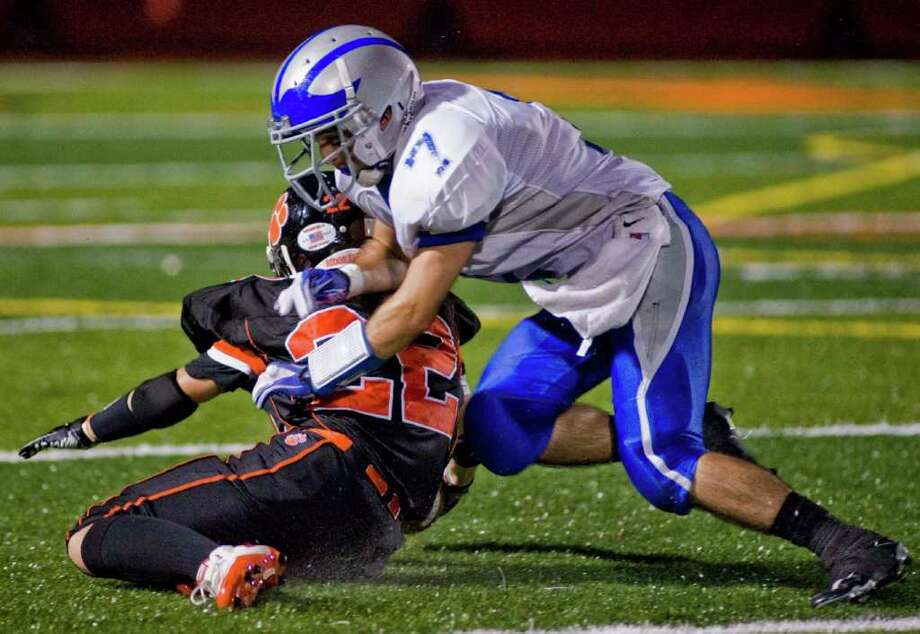 Ridgefield High School's Martin Carbone is taken down by Fairfield Ludlowe's Kyle Broderick in a football game at Ridgefield. Friday, Sept. 23, 2011 Photo: Scott Mullin / The News-Times Freelance