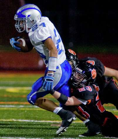 Fairfield Ludlowe's Dan Silvestri tries to avoid the tackle by Ridgefield High School's Neal Hicks during a football game at Ridgefield. Friday, Sept. 23, 2011 Photo: Scott Mullin / The News-Times Freelance