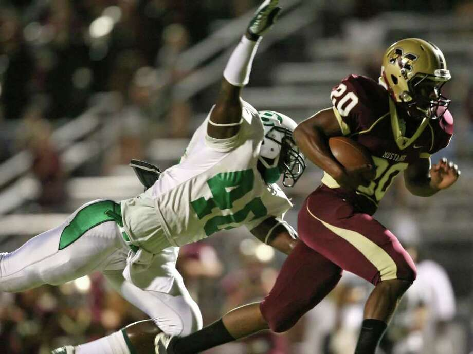 Magnolia West's Desmond Richards (20) runs past the reach of Brenham's Jerid Jeter-Gilman for a 40-yard reception during the first quarter of their game, Friday at Mustang Stadium in Magnolia. Photo: Eric Christian Smith, For The Chronicle