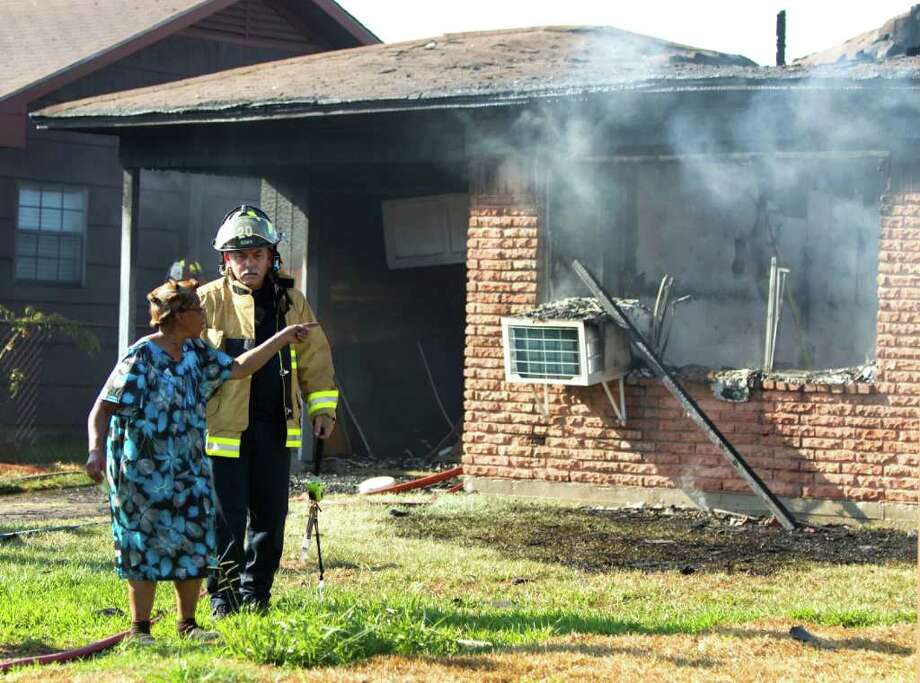 Joyce Robertson, left, walks past her home that was gutted by fire in the 8600 block of Candy Friday, Sept. 23, 2011, in Houston. One man, David Ray Willis, was taken to the hospital for smoke inhalation, his sister Joyce Robinson, who also lives in the home, said. Photo: Brett Coomer, Houston Chronicle / © 2011 Houston Chronicle