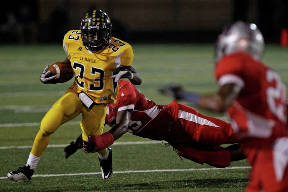 Running back Ja'Core Aldridge #23 of the La Marque Cougars breaks tackles against  the Manvel Mavericks defense in the opening of District 24-4A high school football game at Alvin Memorial Stadium in Alvin, Texas. For the Chronicle: Thomas B. Shea Photo: For The Chronicle: Thomas B. She