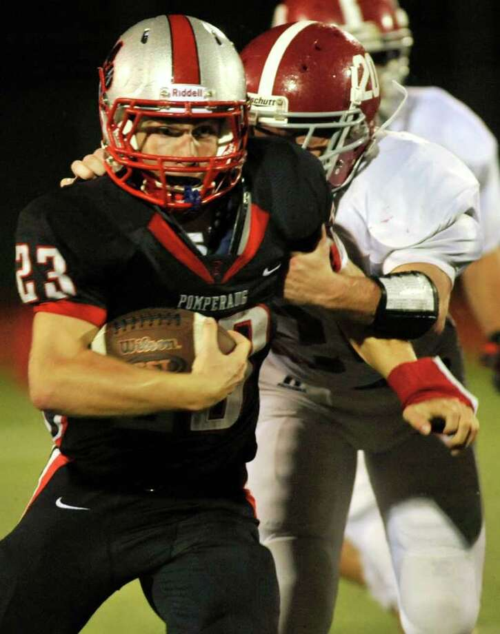 Pomperaug's Dylan McAllister fends off Bethel's William Quinn for a kickoff return during their game at Pomperaug High School in Southbury on Friday, Sept. 23, 2011. Photo: Jason Rearick / The News-Times