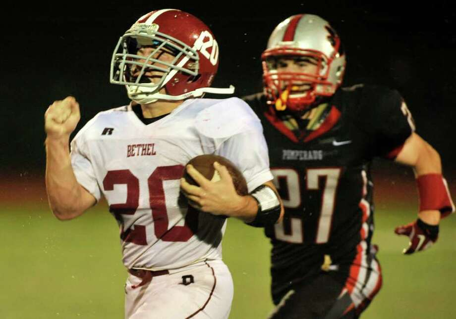 Bethel's William Quinn, left, outruns Pomperaug's Dana Gramolini for their only touchdown during their game at Pomperaug High School in Southbury on Friday, Sept. 23, 2011. Photo: Jason Rearick / The News-Times