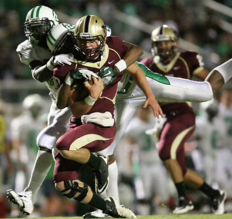 Magnolia West quarterback Tyler Anderson is brought down by Brenham's Desmond Lockett (l) and Robert Felder during the first half of their game, Friday at Mustang Stadium in Magnolia. Photo: Eric Christian Smith, For The Chronicle