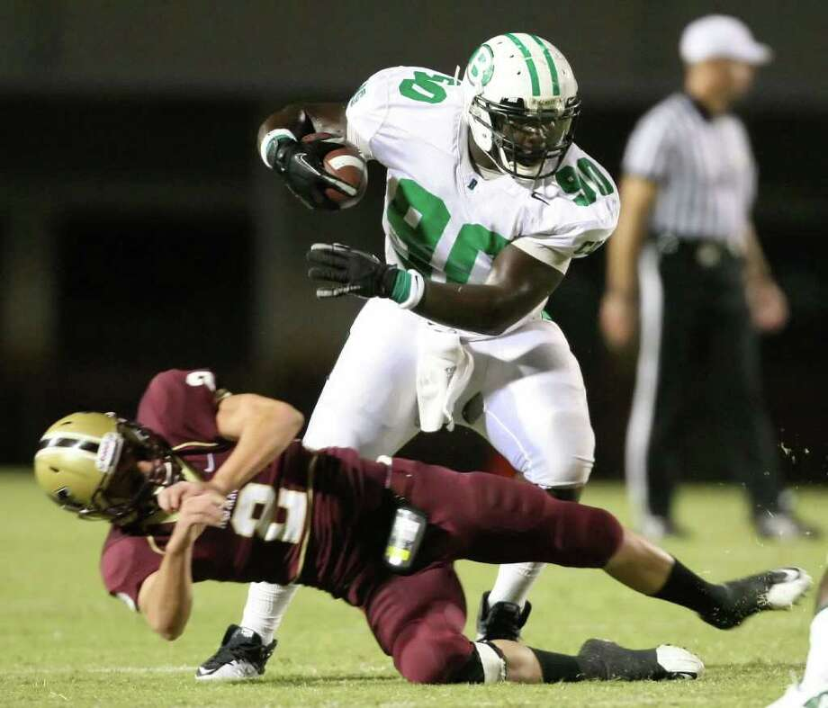 Brenham's Malcom Brown (90) pushes away Magnolia West's Justin Williams en route to a fifty-yard, first quarter touchdown, Friday at Mustang Stadium in Magnolia. Photo: Eric Christian Smith, For The Chronicle
