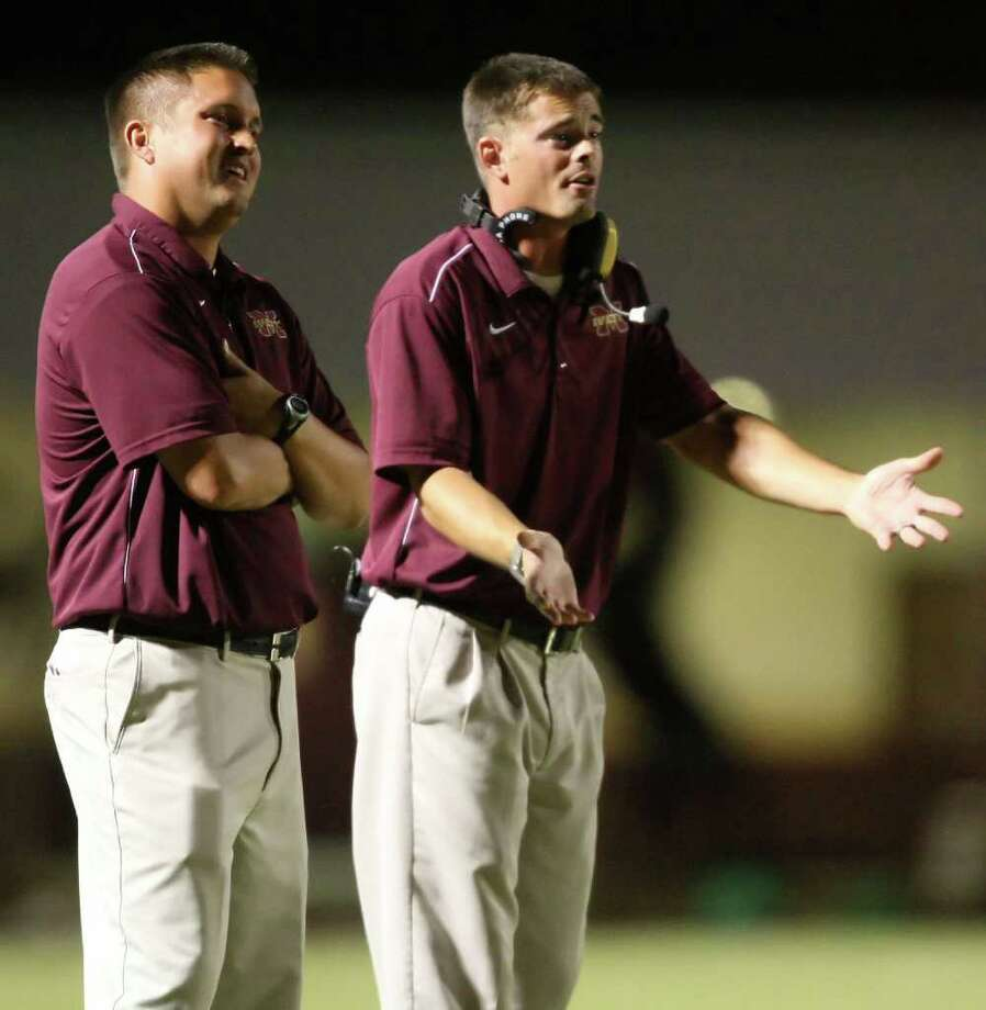 Magnolia West head coach Shawn Bell (left) and assistant coach David Jeffrey look at their players in frustration after a penalty was called against the Mustangs during the first half of their game, Friday at Mustang Stadium in Magnolia. Photo: Eric Christian Smith, For The Chronicle