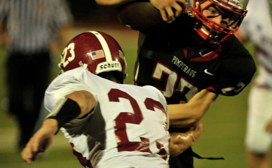 Pomperaug's Dylan McAllister, right, breaks through the tackle of Bethel's Matthew Kessler during their game at Pomperaug High School in Southbury on Friday, Sept. 23, 2011. Photo: Jason Rearick / The News-Times
