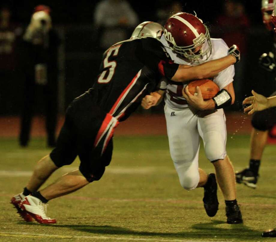 Bethel's William Quinn, right, runs the ball into Pomperaug's Matt Paola during their game at Pomperaug High School in Southbury on Friday, Sept. 23, 2011. Photo: Jason Rearick / The News-Times