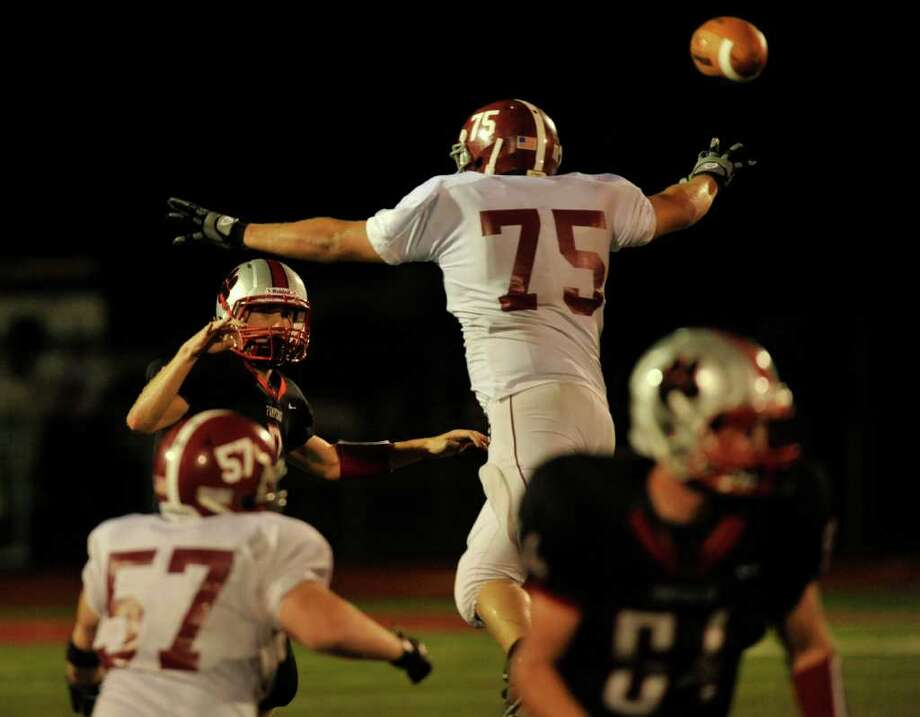Bethel's Thiago Lanes, right, pressures Pomperaug quarterback Eric Beatty during their game at Pomperaug High School in Southbury on Friday, Sept. 23, 2011. Photo: Jason Rearick / The News-Times