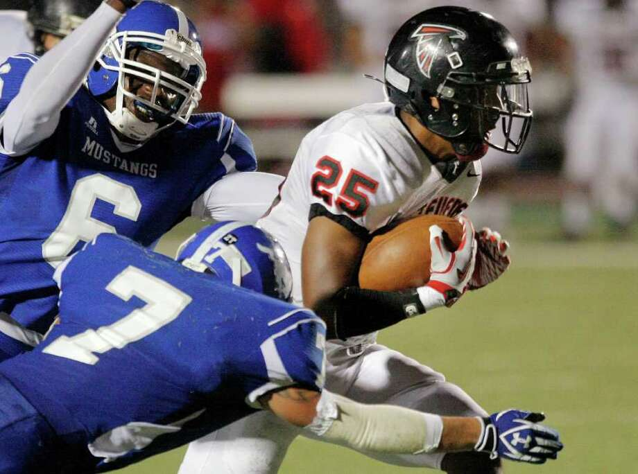 Stevens' Derek Mann, right, is brought down by John Jay's Denzell Lloyd, left, and Elizer Cruz during a District 27-5A high school football game, Friday, Sept. 23, 2011, at Gustafson Stadium in San Antonio. Photo: Darren Abate, Express-News