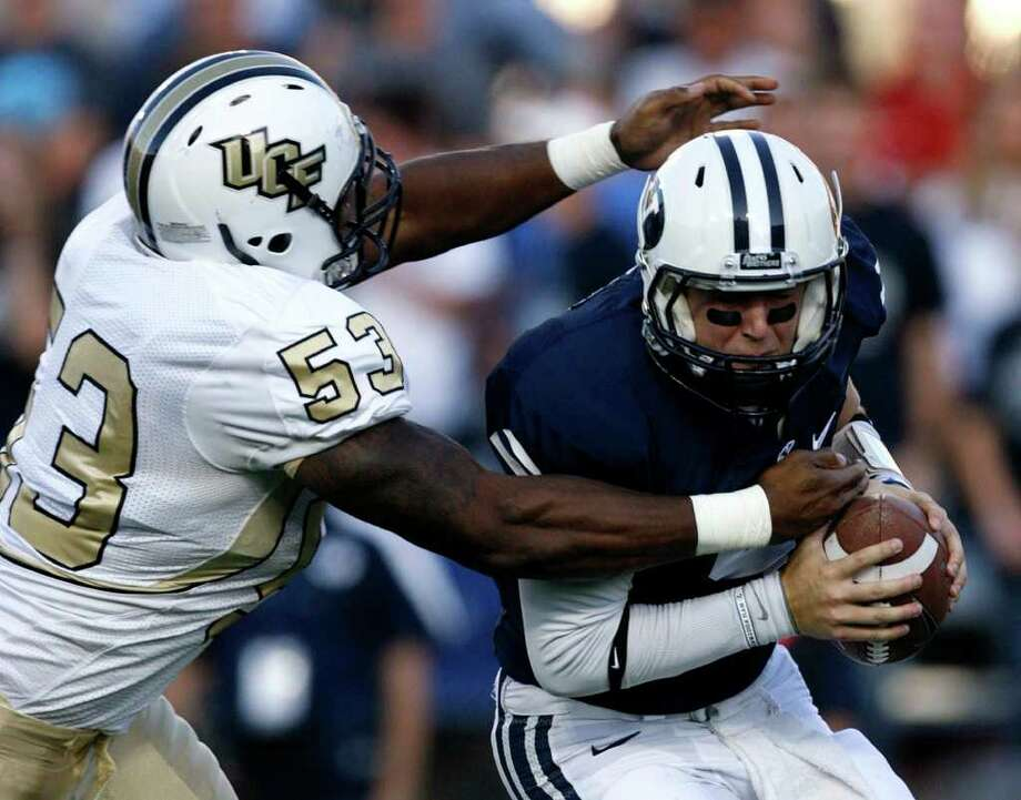 TRENT NELSON : ASSOCIATED PRESS A LITTLE HELP: BYU quarterback Jake Heaps, right, was sacked by Central Florida's Darius Nall, but his offense had some help in a 24-17 victory in Provo, Utah. Photo: Trent Nelson / 2011 Trent Nelson