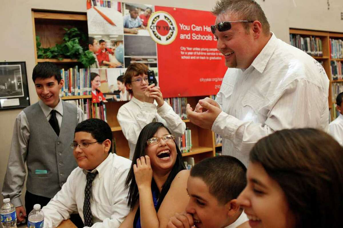 Russell Rush, of 'The Russell Rush Show' on Mix 96.1, laughs with Avid class students including Minerva Hernandez, 14, center, after Mayor Julian Castro held a press conference announcing the Wake Up! Initiative for San Antonio at Mark Twain Middle School in San Antonio on Friday, Sept. 23. 2011. Rush recorded one of the wake up calls to kick off the program.