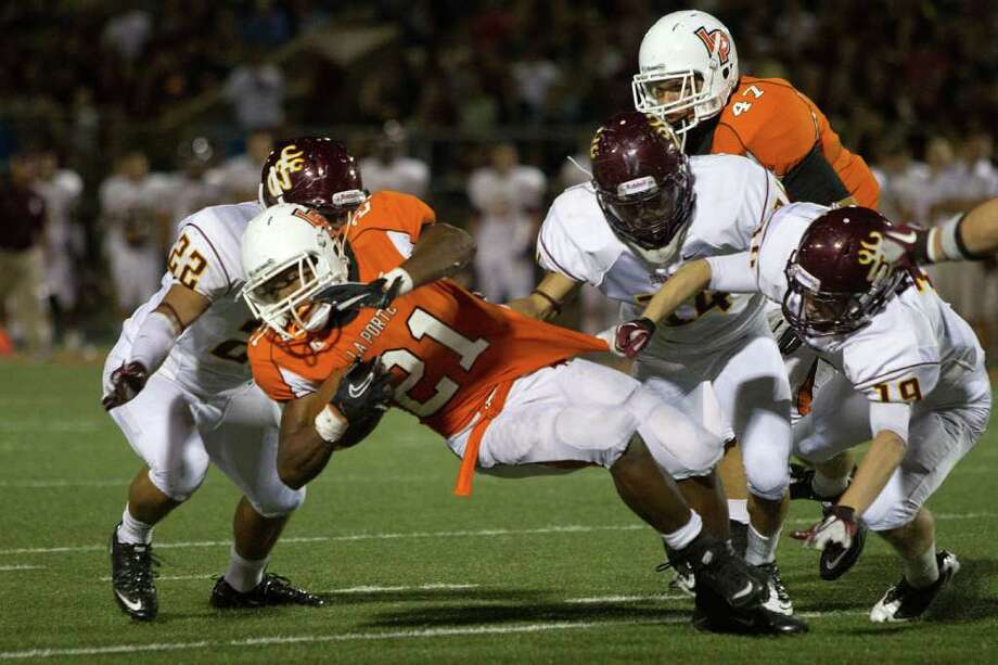 La Porte running back Keith Whitely (21) is brought down by Deer Park defenders Vincent Vega (22), Ryan Martinez (14) and Jermy Halling (19). Photo: Smiley N. Pool, Houston Chronicle / © 2011  Houston Chronicle
