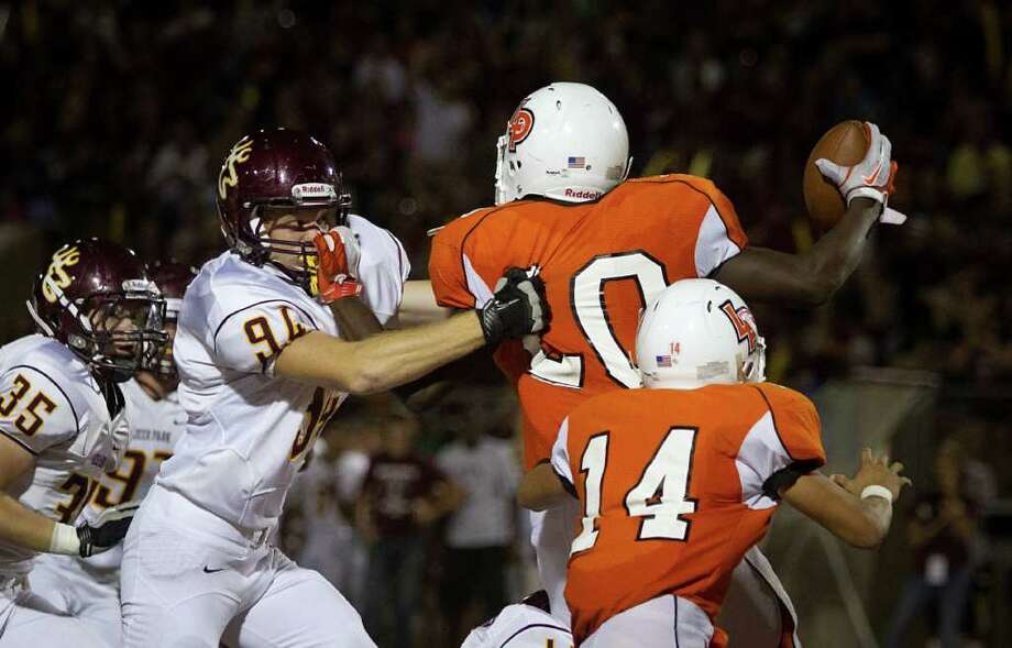 La Porte running back  Hoza Scott (20) grabs the facemask of Deer Park defensive lineman Ryan Davis (94) as he barely gets off a pass to avoid being dropped in the end zone for a safety during the second half. Photo: Smiley N. Pool, Houston Chronicle / © 2011  Houston Chronicle