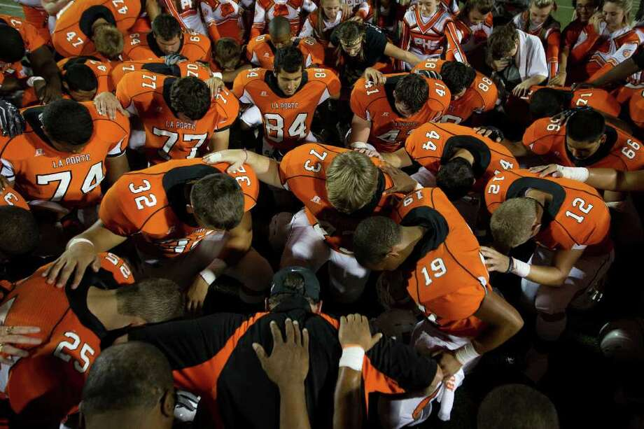 La Porte players kneel in prayer after their overtime victory over rival Deer Park. Photo: Smiley N. Pool, Houston Chronicle / © 2011  Houston Chronicle