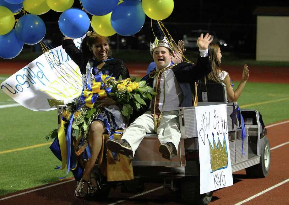 Alamo Heights homecoming king Drew Boynton (right) joined by newly crown homecoming queen Katrina Johnson (left) wave as they take a ride in a cart around the stadium during halftime ceremonies at Alamo Heights High School on Friday, Sept. 23, 2011. Boynton who has Down syndrome was selected by the entire school to be the king at homecoming. Photo: KIN MAN HUI, Kin Man Hui/kmhui@express-news.net / SAN ANTONIO EXPRESS-NEWS