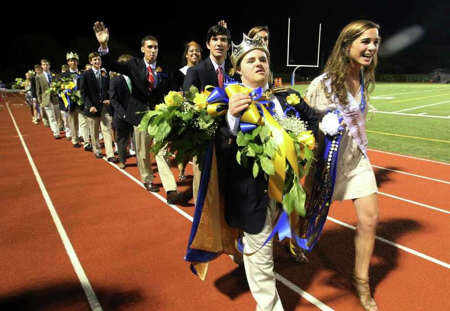 Alamo Heights homecoming king Drew Boynton (center) joined by homecoming court duchess Lena Carr (right) leads the rest of the court to start the school's homecoming ceremonies during halftime of their football game against Lockhart High at Alamo Heights High School on Friday, Sept. 23, 2011. Boynton who has Down syndrome was selected by the entire school to be the king at homecoming. Photo: KIN MAN HUI, Kin Man Hui/kmhui@express-news.net / SAN ANTONIO EXPRESS-NEWS