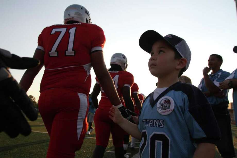 Shadow Creek Ranch Titans pee wee football player Arman Sarssob age 7, shakes hands with the Manvel Mavericks before the played against the La Marque Cougars in the opening of District 24-4A high school football game at Alvin Memorial Stadium in Alvin, Texas. For the Chronicle: Thomas B. Shea Photo: For The Chronicle: Thomas B. She