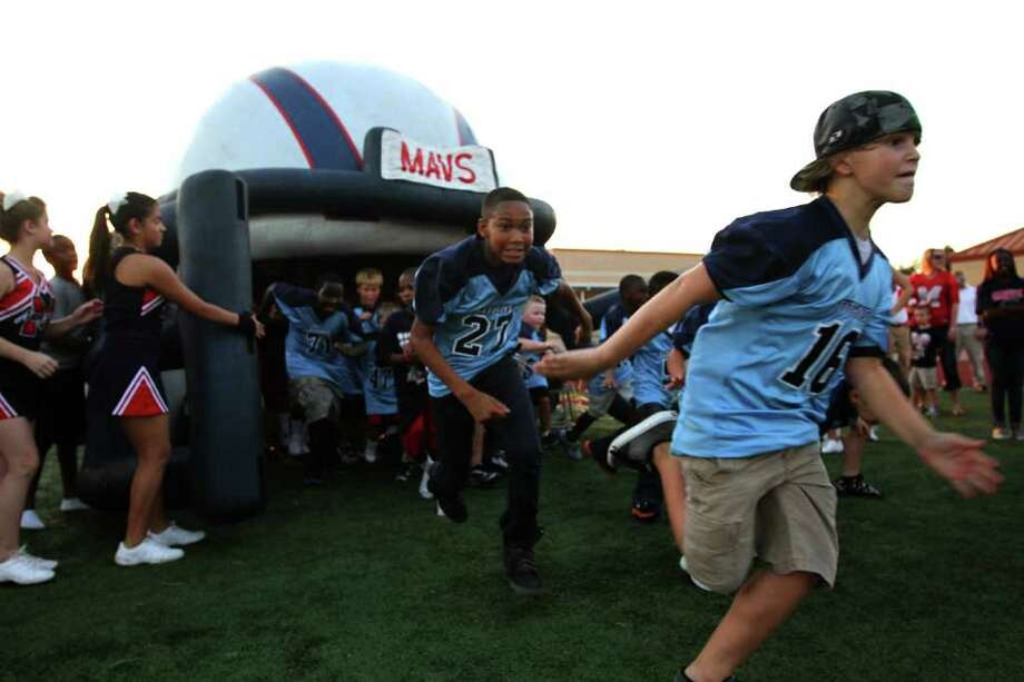 Shadow Creek Ranch Titans pee wee footballs run out of the helmet before Manvel Mavericks played against the La Marque Cougars in the opening of District 24-4A high school football game at Alvin Memorial Stadium in Alvin, Texas. For the Chronicle: Thomas B. Shea Photo: For The Chronicle: Thomas B. She
