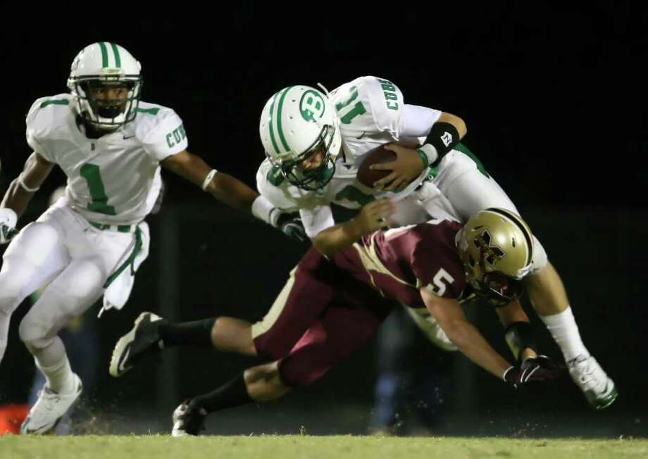 Brenham's Dean Haveman (10) is tackled by Magnolia West's Jeremy Jordan as teammate Tremond Moore looks on during the first half of their game, Friday at Mustang Stadium in Magnolia. Photo: Eric Christian Smith, For The Chronicle