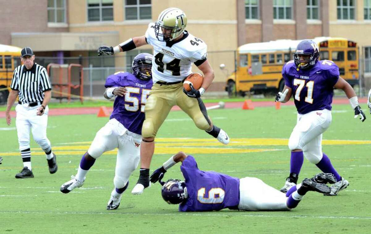 Trumbull's Don Cherry (44) carries the ball for yardage leaping over Westhill's Ryan Burke (6) during the football game at Westhill High School in Stamford on Saturday, Sept. 24, 2011.