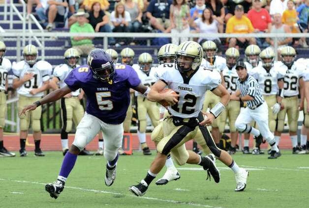 Trumbull's Brendan Moore (12) carries the ball for yardage as Westhill's Dylan Moye (5) defends during the football game at Westhill High School in Stamford on Saturday, Sept. 24, 2011. Photo: Amy Mortensen / Connecticut Post Freelance