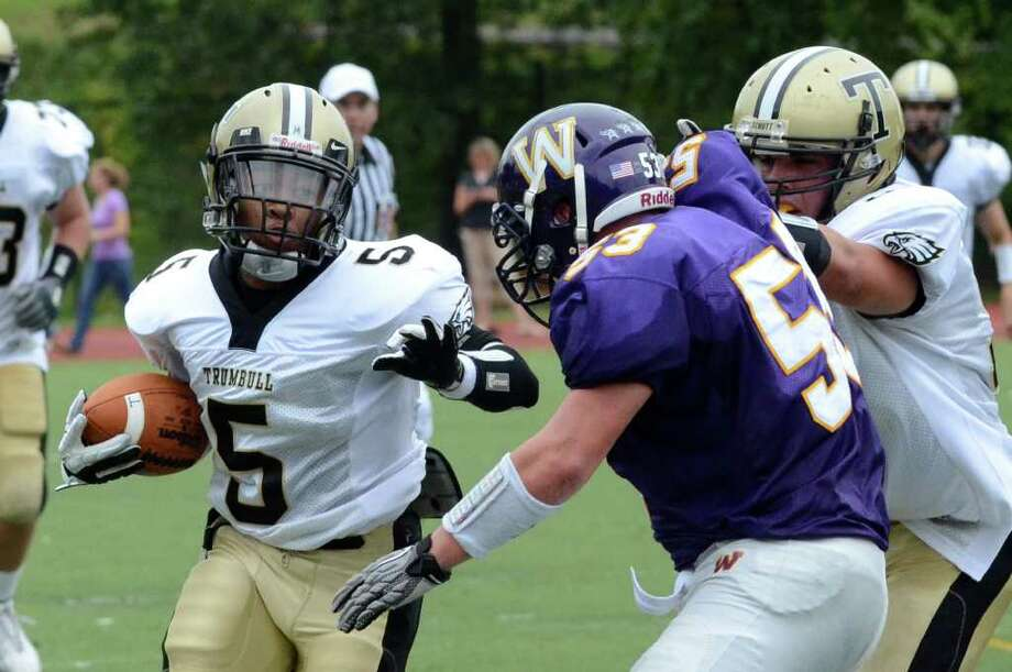 Trumbull's J.J. Smart (5) carries the ball as teammate Joe Ormsbee stops Westhill defender Chris Soule (53) during the football game at Westhill High School in Stamford on Saturday, Sept. 24, 2011. Photo: Amy Mortensen / Connecticut Post Freelance