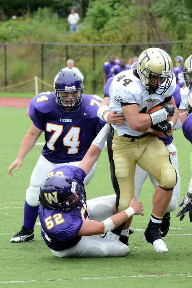 Westhill's Seamus Ronan (52) and Mike Vigliotti (hidden behind Cherry) take down Trumbull's Don Cherry (44) during the football game at Westhill High School in Stamford on Saturday, Sept. 24, 2011. Photo: Amy Mortensen / Connecticut Post Freelance