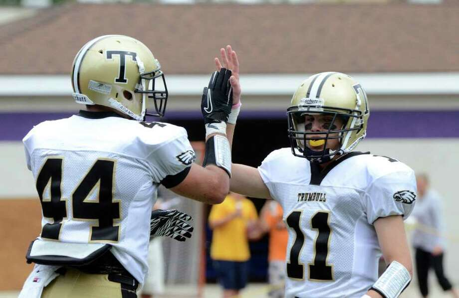 Trumbull's Daniel Paolino (11) congratulates teammate Don Cherry on a touchdown during the football game against Westhill at Westhill High School in Stamford on Saturday, Sept. 24, 2011. Photo: Amy Mortensen / Connecticut Post Freelance