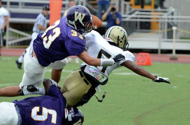 Trumbull's J.J. Smart (5) is knocked to the ground by Westhill's Dylan Moye (5) and Nick Jimenez (33) during the football game at Westhill High School in Stamford on Saturday, Sept. 24, 2011. Photo: Amy Mortensen / Connecticut Post Freelance