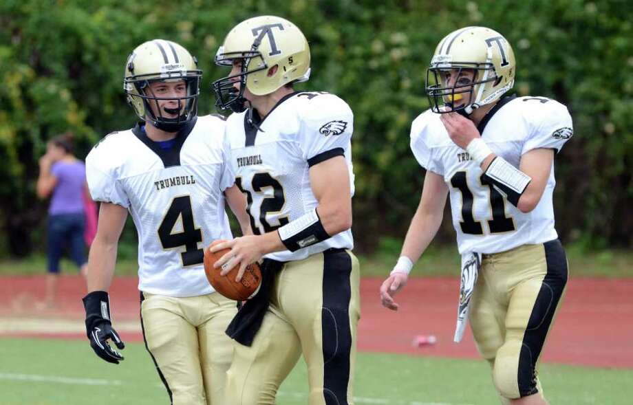 Trumbull's Jeff Jarboe (4) and Daniel Paolino (11) walk over to congratulate teammate Brendan Moore on a touchdown during the football game against Westhill at Westhill High School in Stamford on Saturday, Sept. 24, 2011. Photo: Amy Mortensen / Connecticut Post Freelance