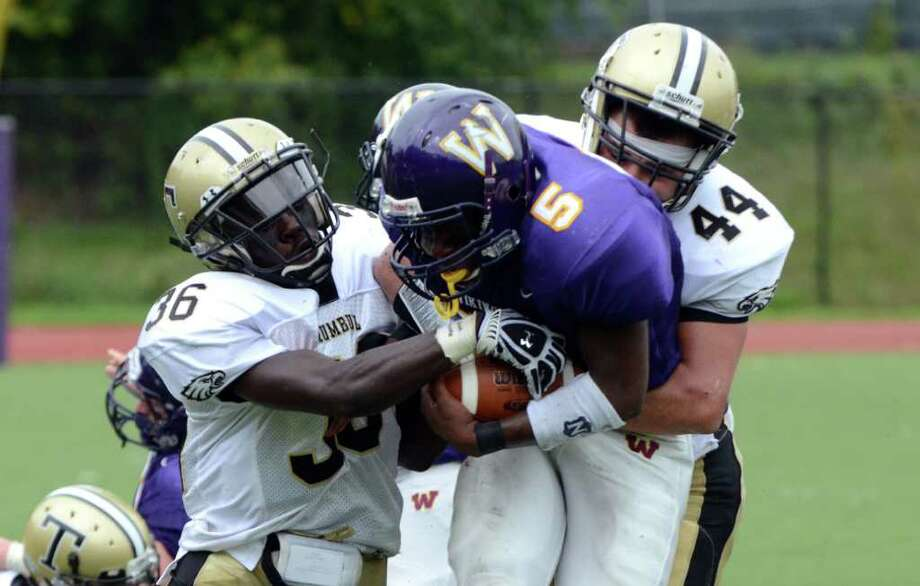 Trumbull's Seon Ramsay (36) and Don Cherry (44) bring down Westhill's Dylan Moye during the football game at Westhill High School in Stamford on Saturday, Sept. 24, 2011. Photo: Amy Mortensen / Connecticut Post Freelance